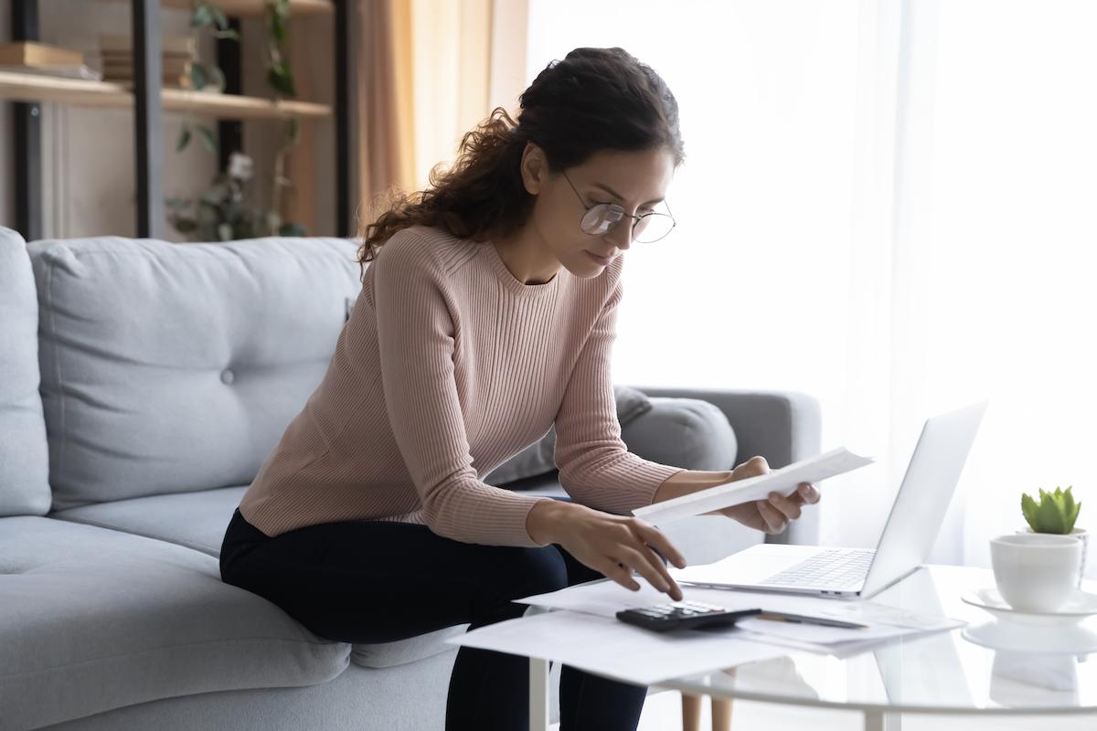 SaaS metrics: Bespectacled woman calculating bills in her living room