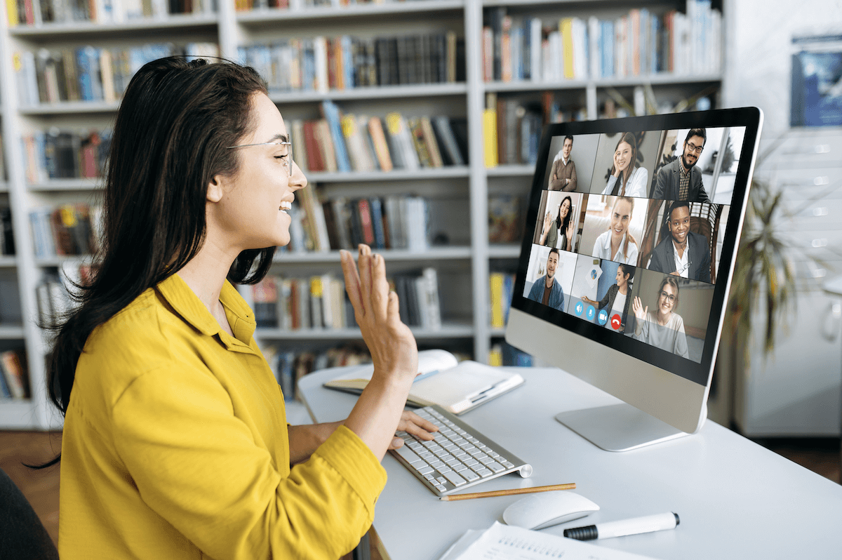 customer onboarding: Smiling woman waving her hand during a video conference