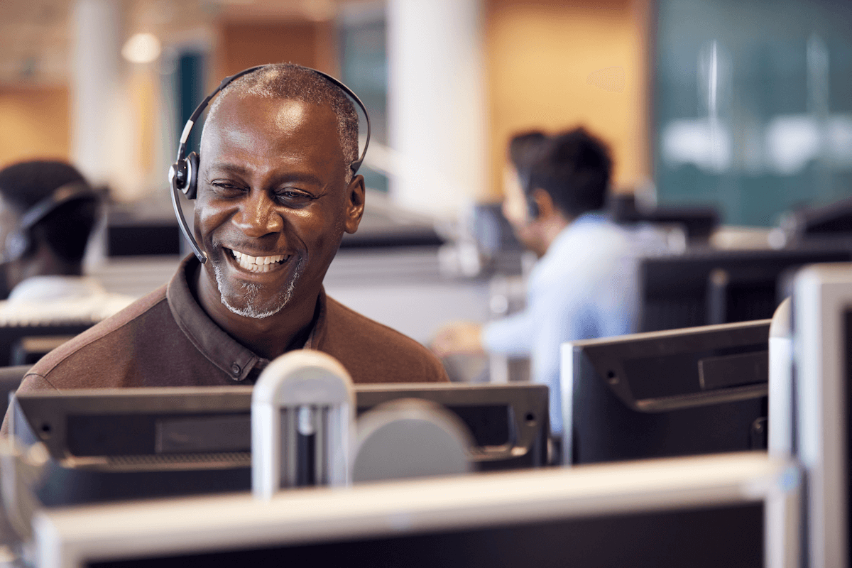 customer onboarding: Smiling man wearing a headset while looking at his monitor