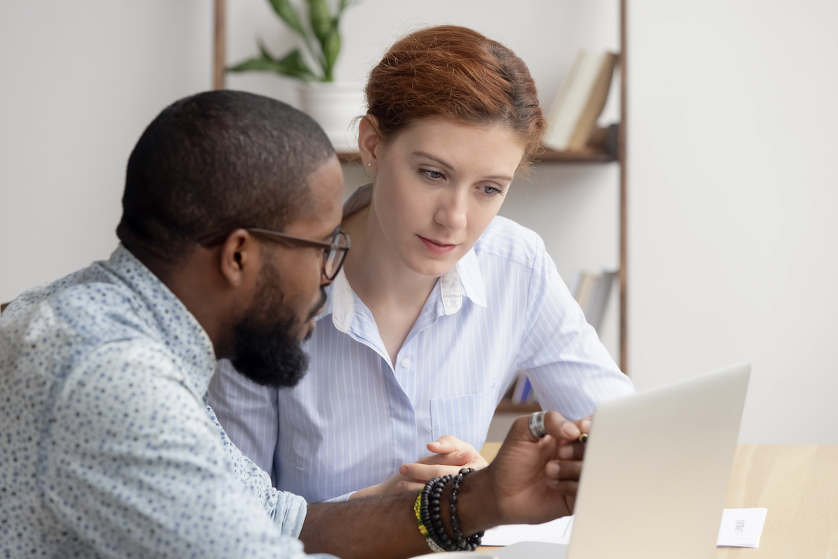 SaaS sales: two people discussing in front of a laptop