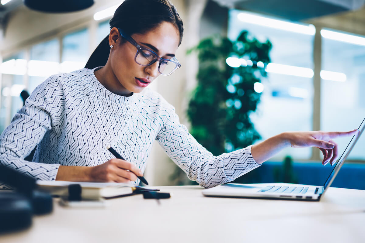 BANT: woman comparing data from her computer vs. her notes