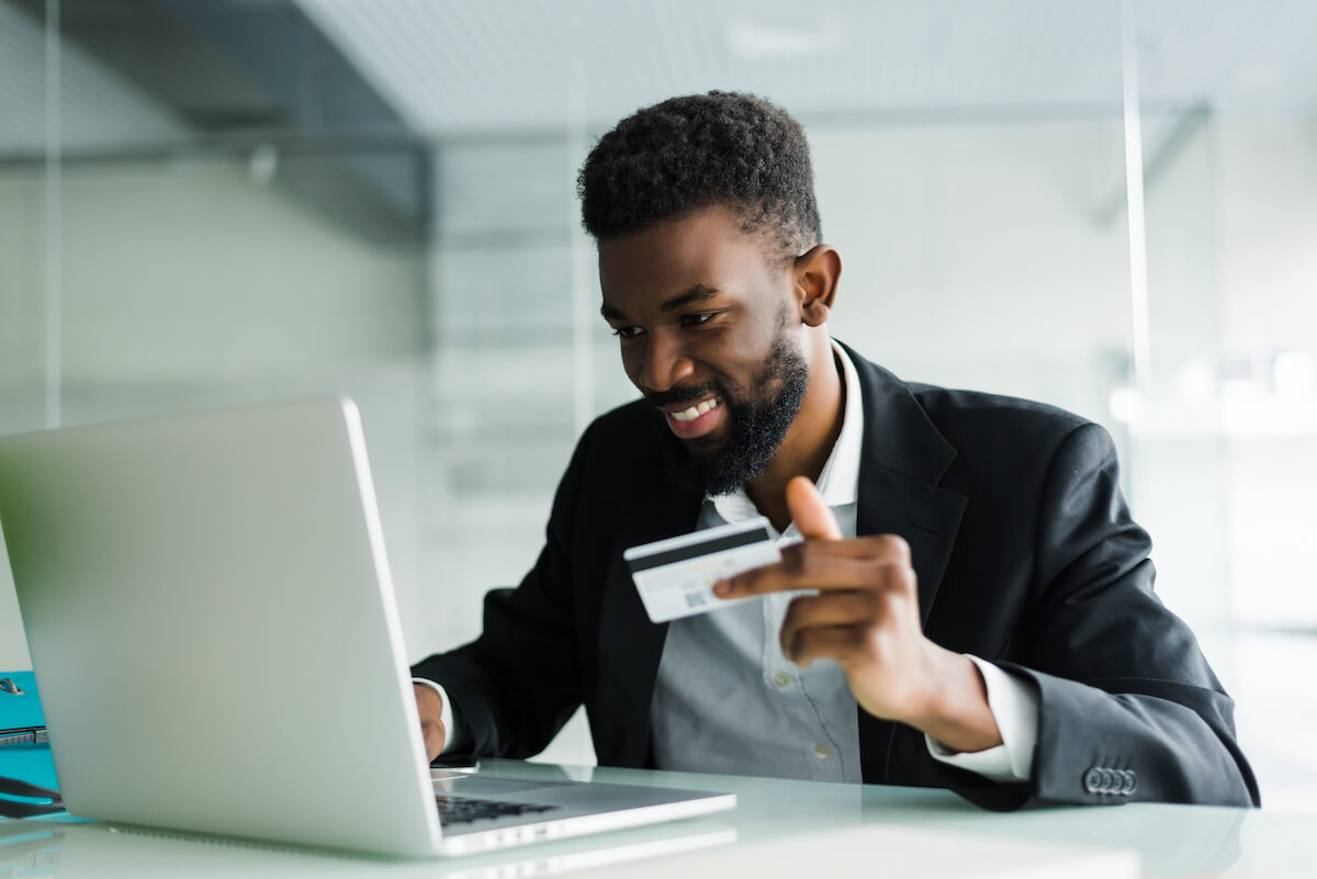 Smiling man purchasing online and holding his credit card