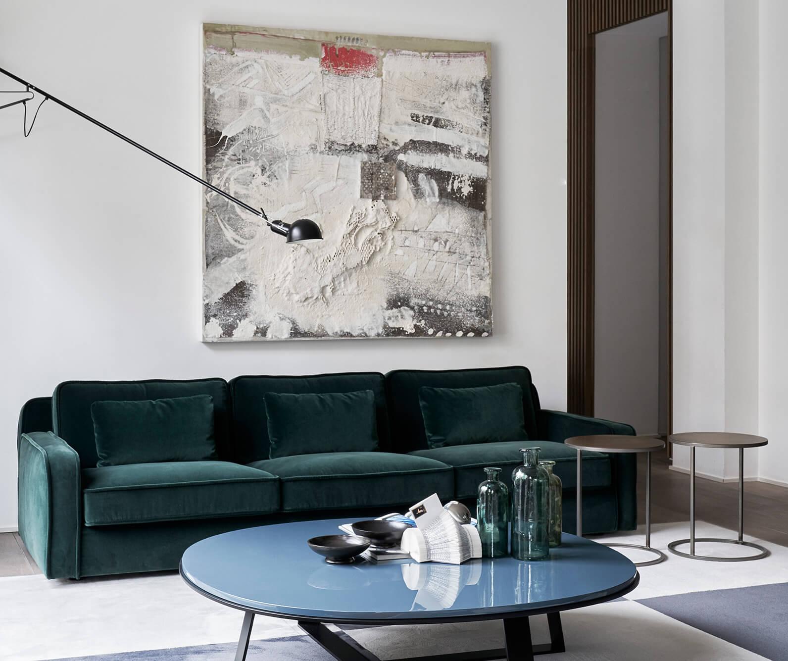 Grünes Sofa mit Couchtisch und Gemälde an der Wand
