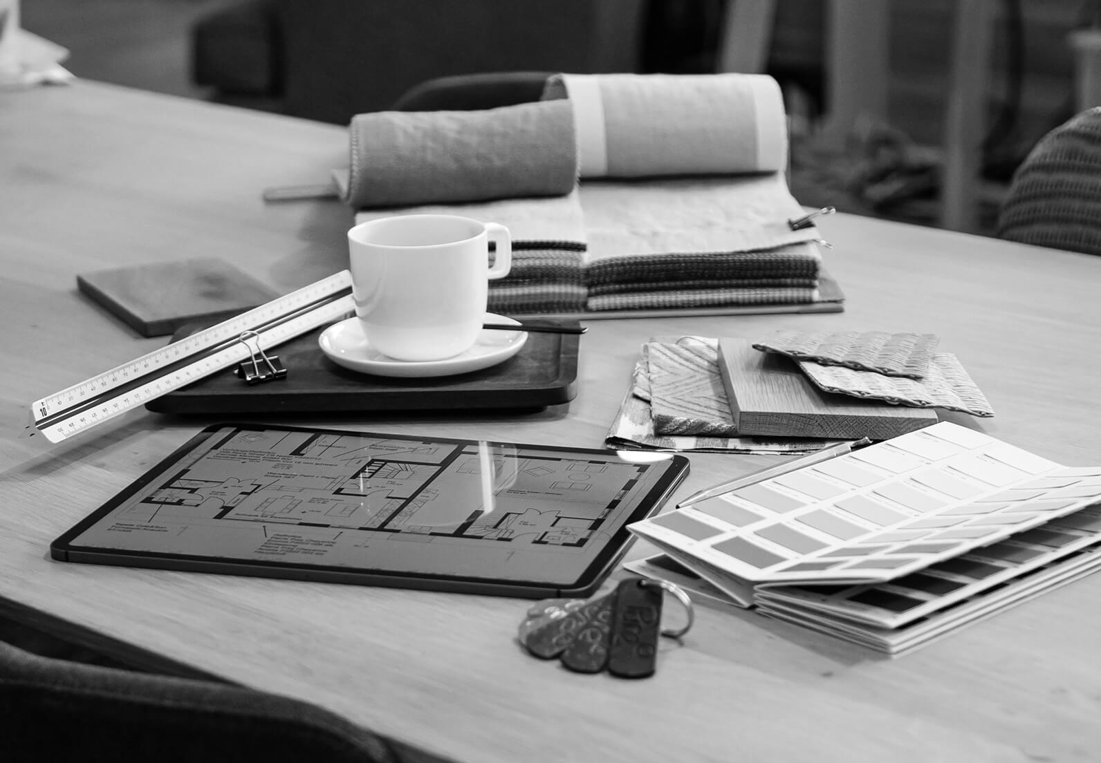 Tisch mit Planungsmitteln wie z.B. iPad, Zollstock, Stoffen und Farben
