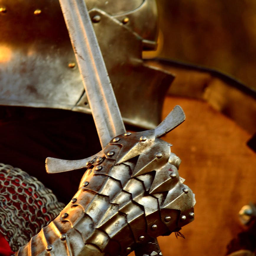 The gauntlet of a knight clutches a readied sword.
