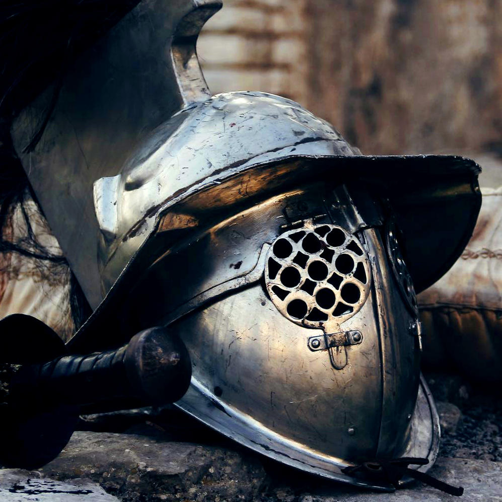 A medieval helmet rests adjacent to a hilt.