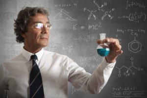 Academic Scientist Marvels At Blue Chemical Reaction Near Chalkboard