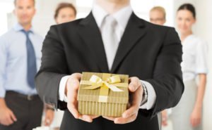 Business Man Holds Out Wrapped Gold Gift For Unknown Employee