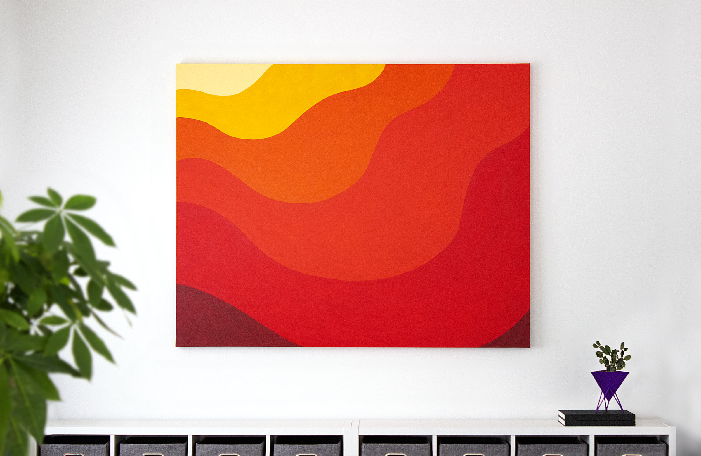 A large canvas painted with a gradation of yellow to orange to read, hanging on a white wall in a modern office.