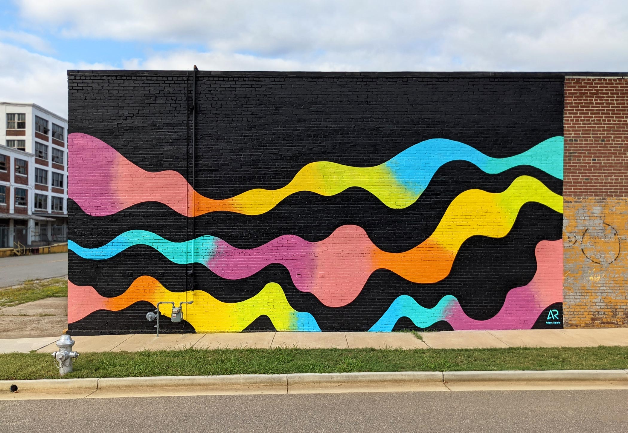 Black painted brick wall with color gradients flowing across it horizontally.