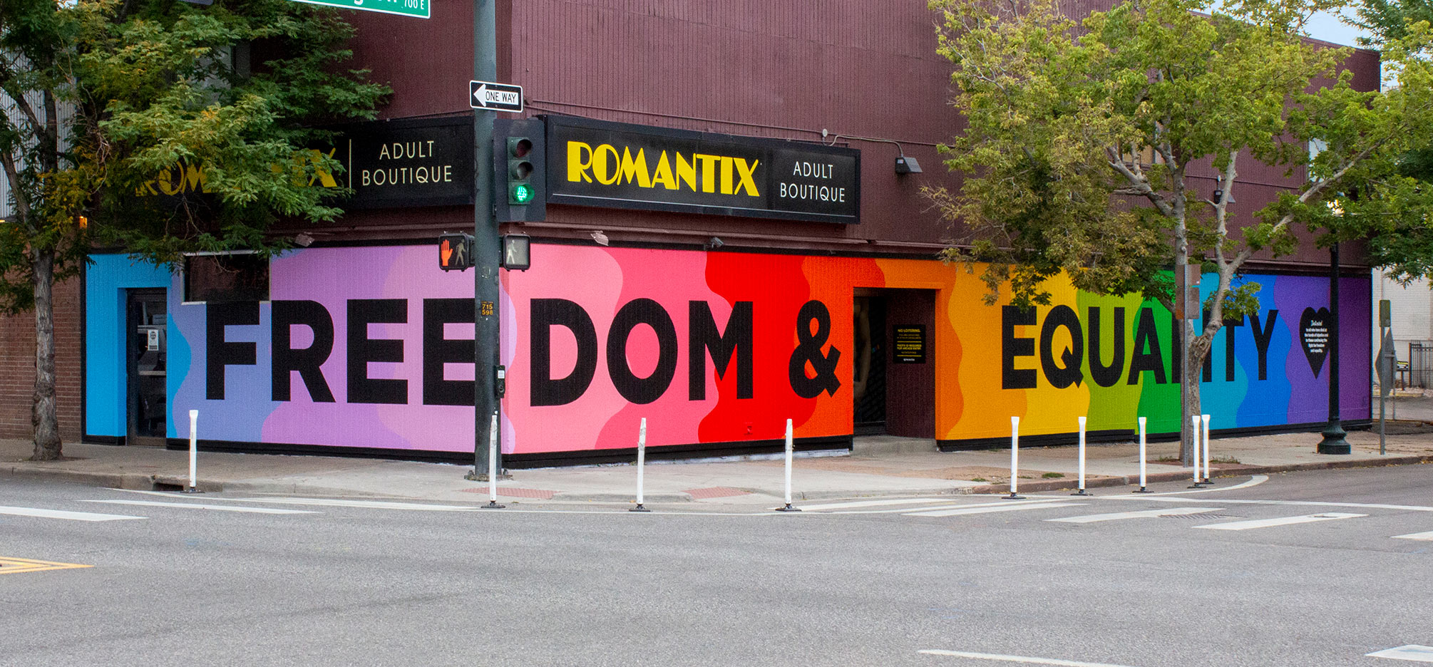 """A mural on the corner of a building. The background of the mural has a horizontal gradation of the pride flag colors with big black letters that reads, """"FREEDOM & EQUALITY"""". With a black heart and white letters on top that reads, """"Dedicated to all who have died at the hands of injustice and for those continuing the fight for freedom and equality."""""""