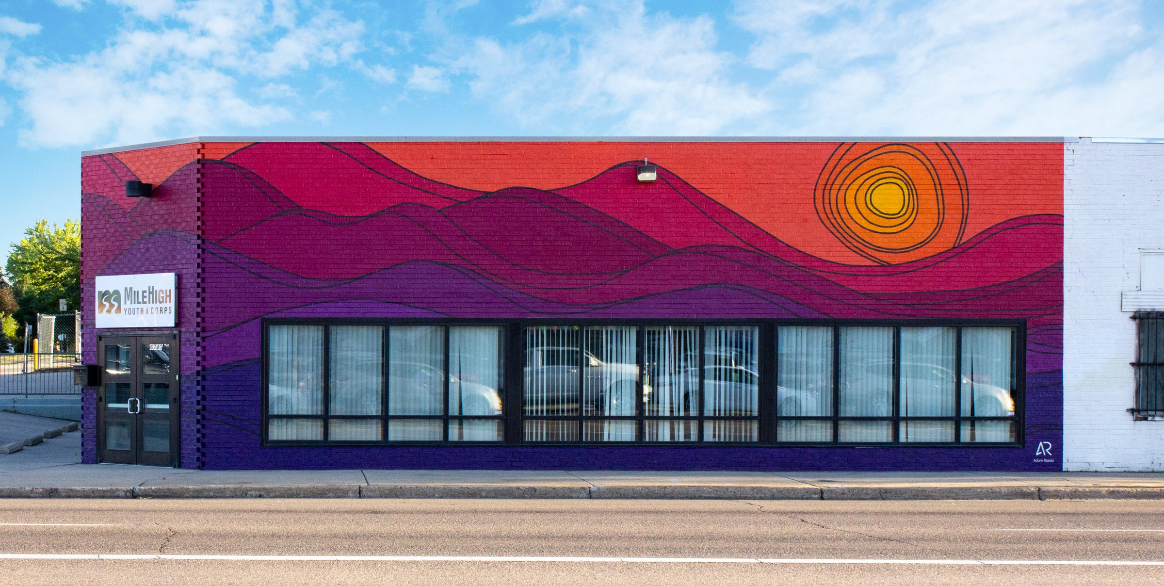 A mural on a brick building that depicts an abstract sunset over purple mountains.