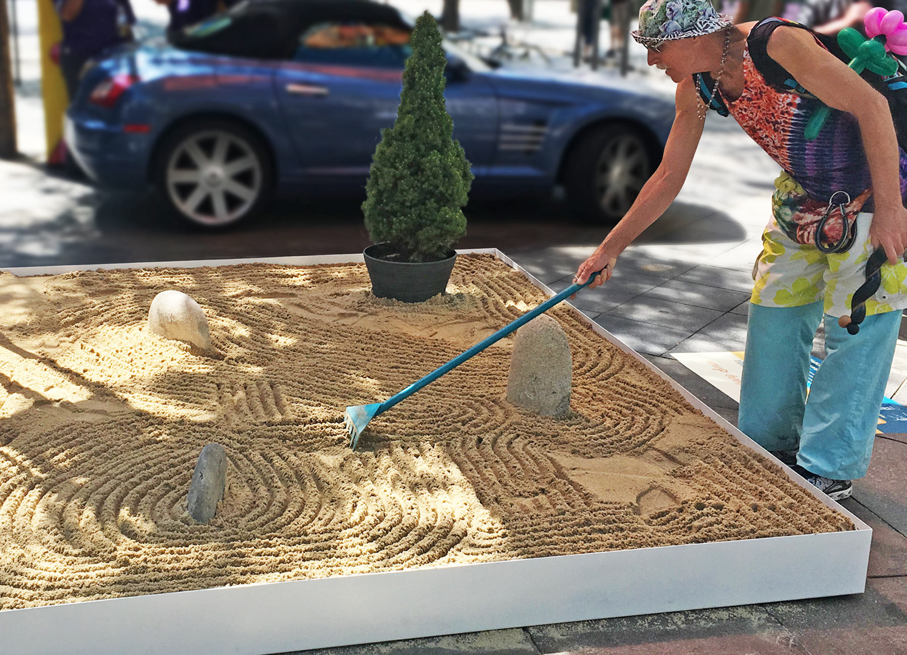 On a warm summer day, a man is using a custom-designed rake to make calming line in sand inside a custom-build zen garden on the 16th street mall in Denver, Colorado.
