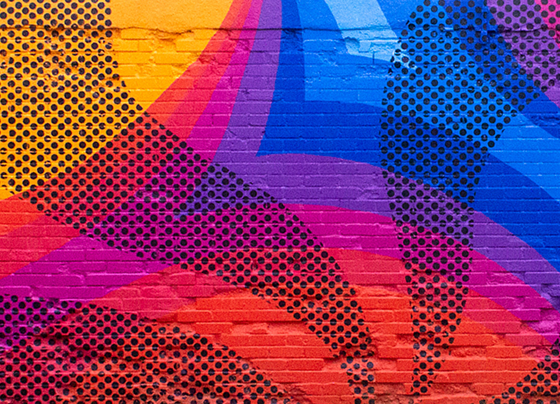 A mural painted on an old brick garage. The design has gradated circles changing from yellow to pink to blue with wavy rays with black polka dot pattern.