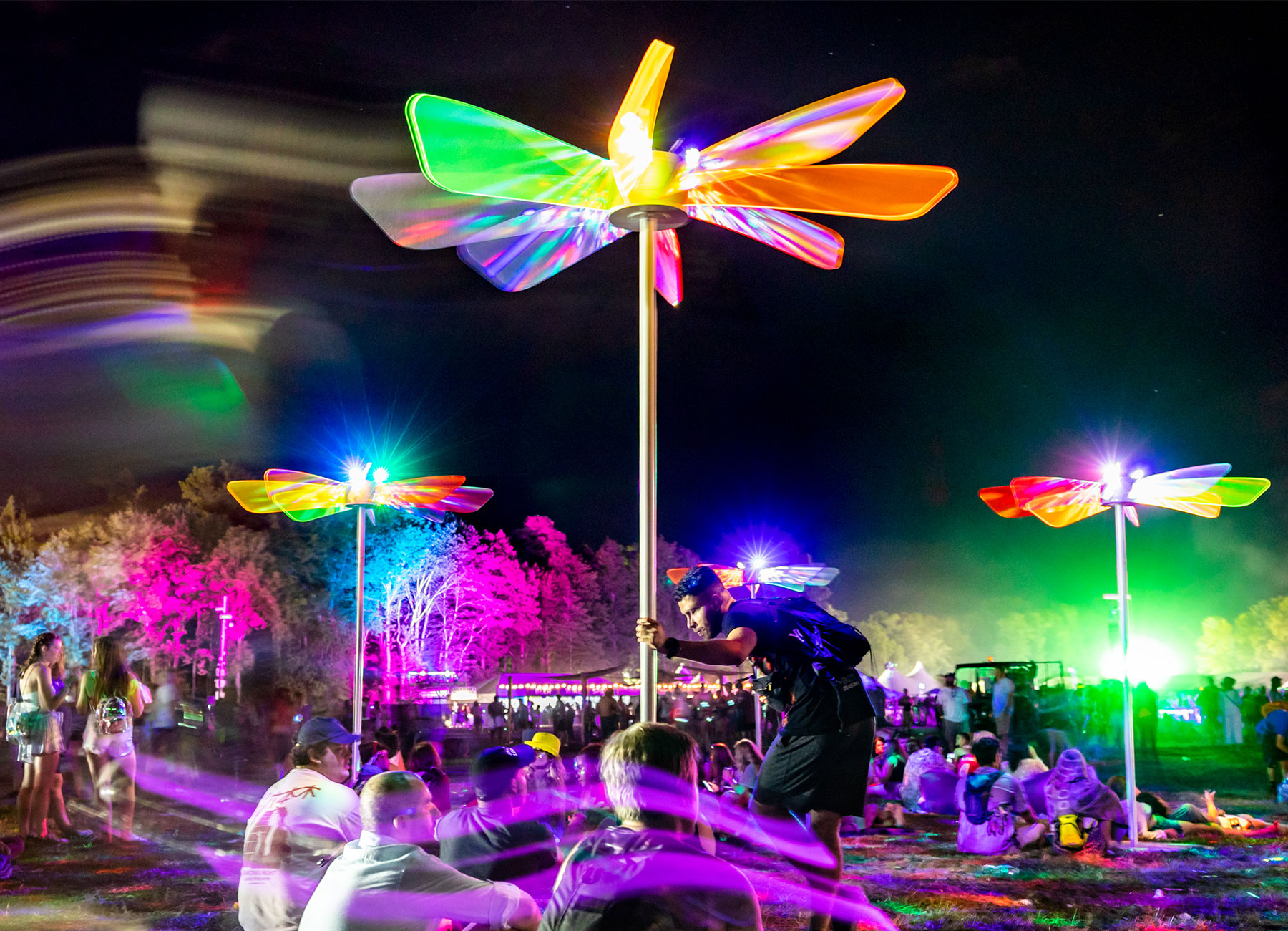 An art installation with 4 colorful structures with acrylic wing blades on top of a pole