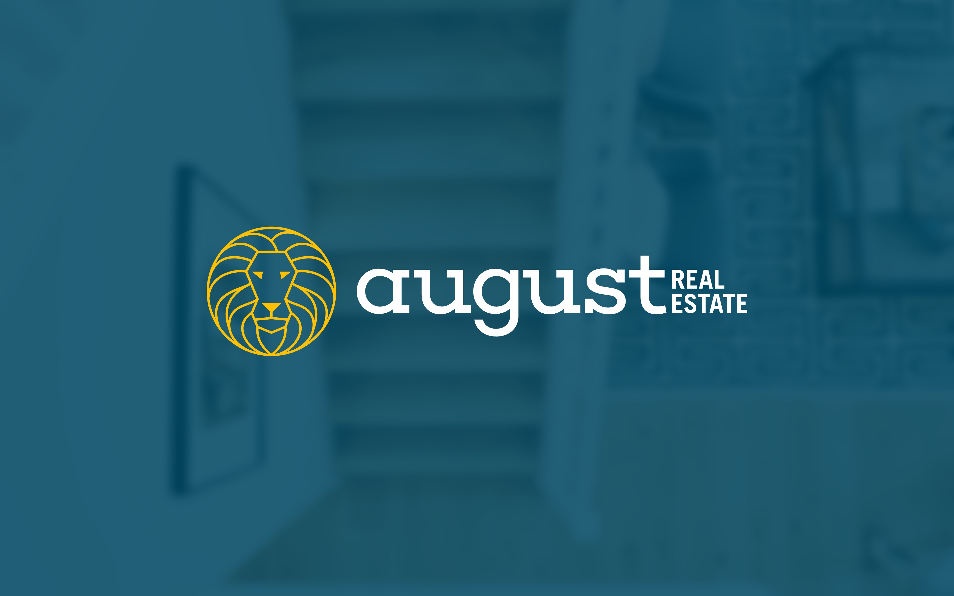 August Real Estate logo on top of a blue overlay aerial view of a modern interior living room
