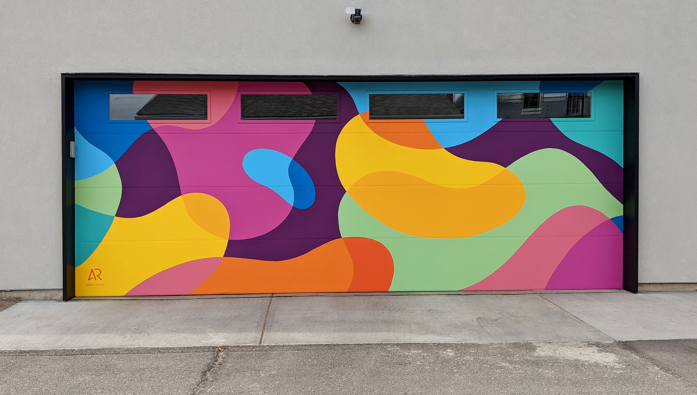 A mural painted on a garage door with abstract colored blobs