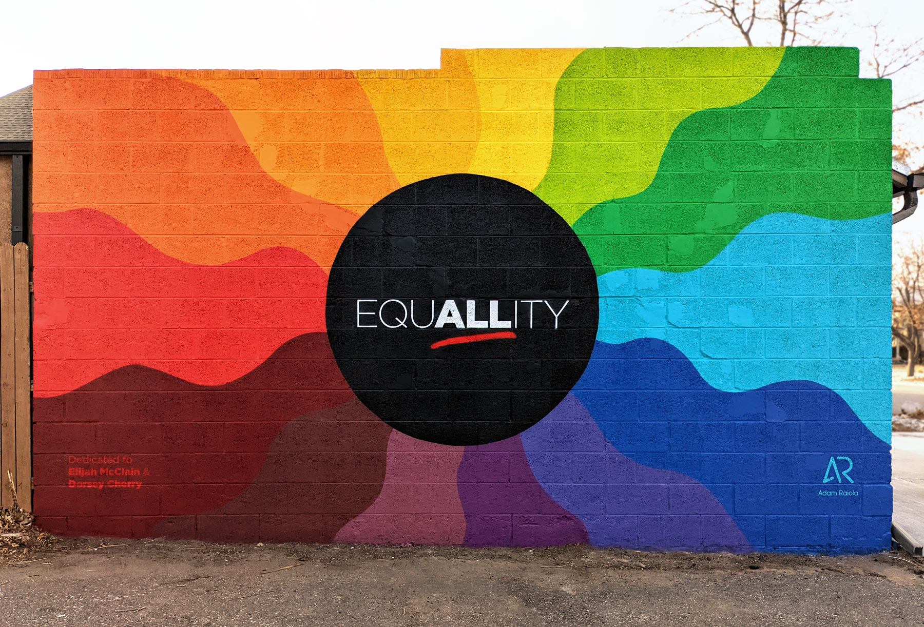 """The side of a garage painted with a mural. In the center is a black circle with white lettering in all caps that reads, """"EQUALLITY"""". The """"ALL"""" part in underlined in red. Behind the black circle is a rainbow of wavy color strips."""