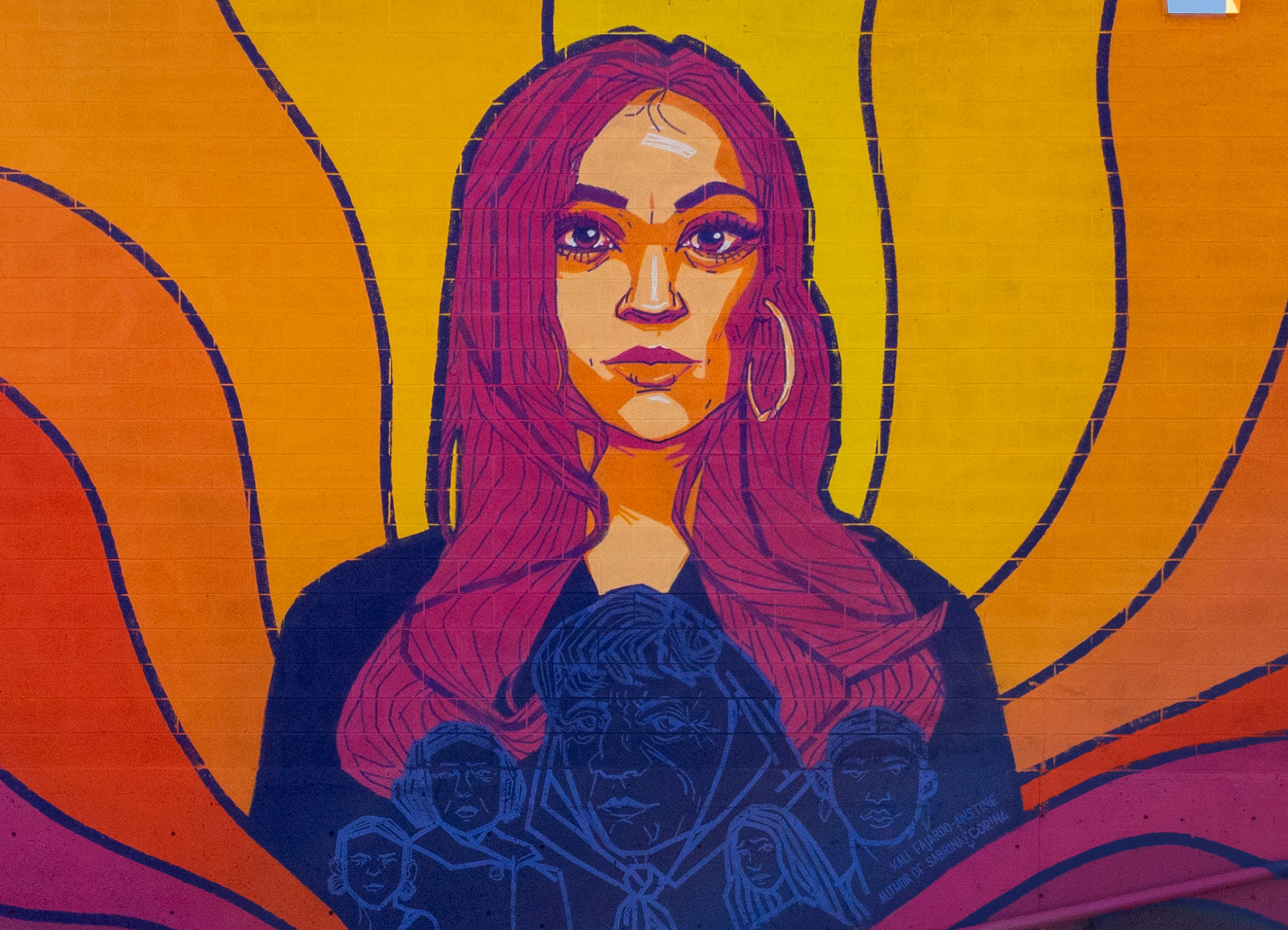 A mural that consists of a portrait of Kali Fajardo-Anstine in a painted stylized illustration with yellow, orange and purple abstract sun rays behind her.