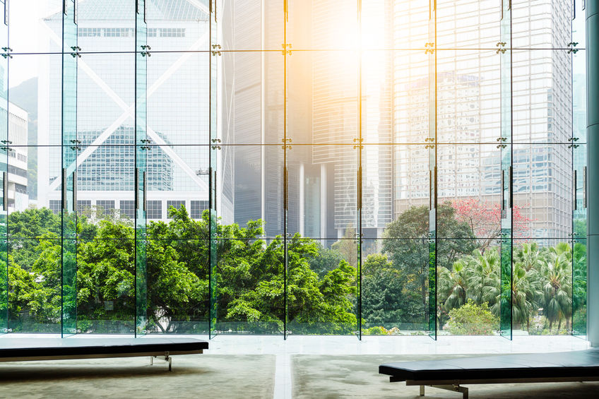 Background image of an office lobby with a giant glass wall showing a lush garden