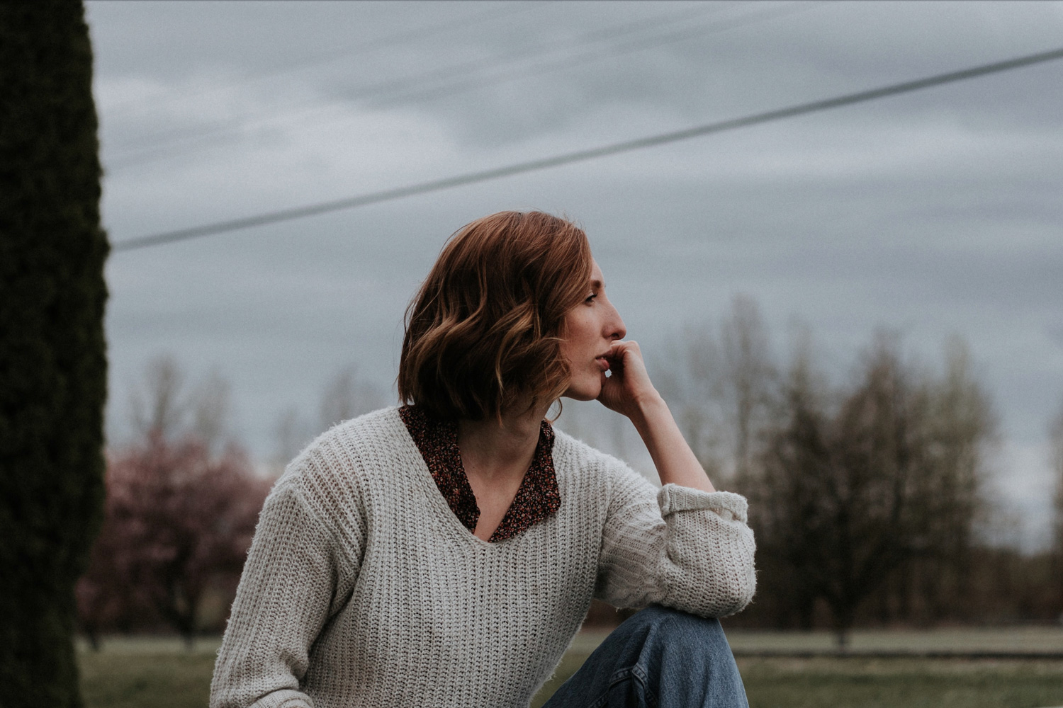 A woman outdoors looking thoughtful