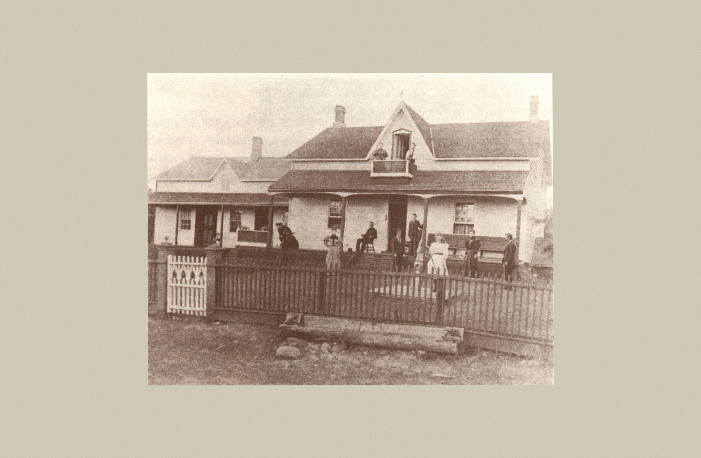 An old house with family sitting on the front porch, balcony, and lawn surrounded by a wrought iron fence