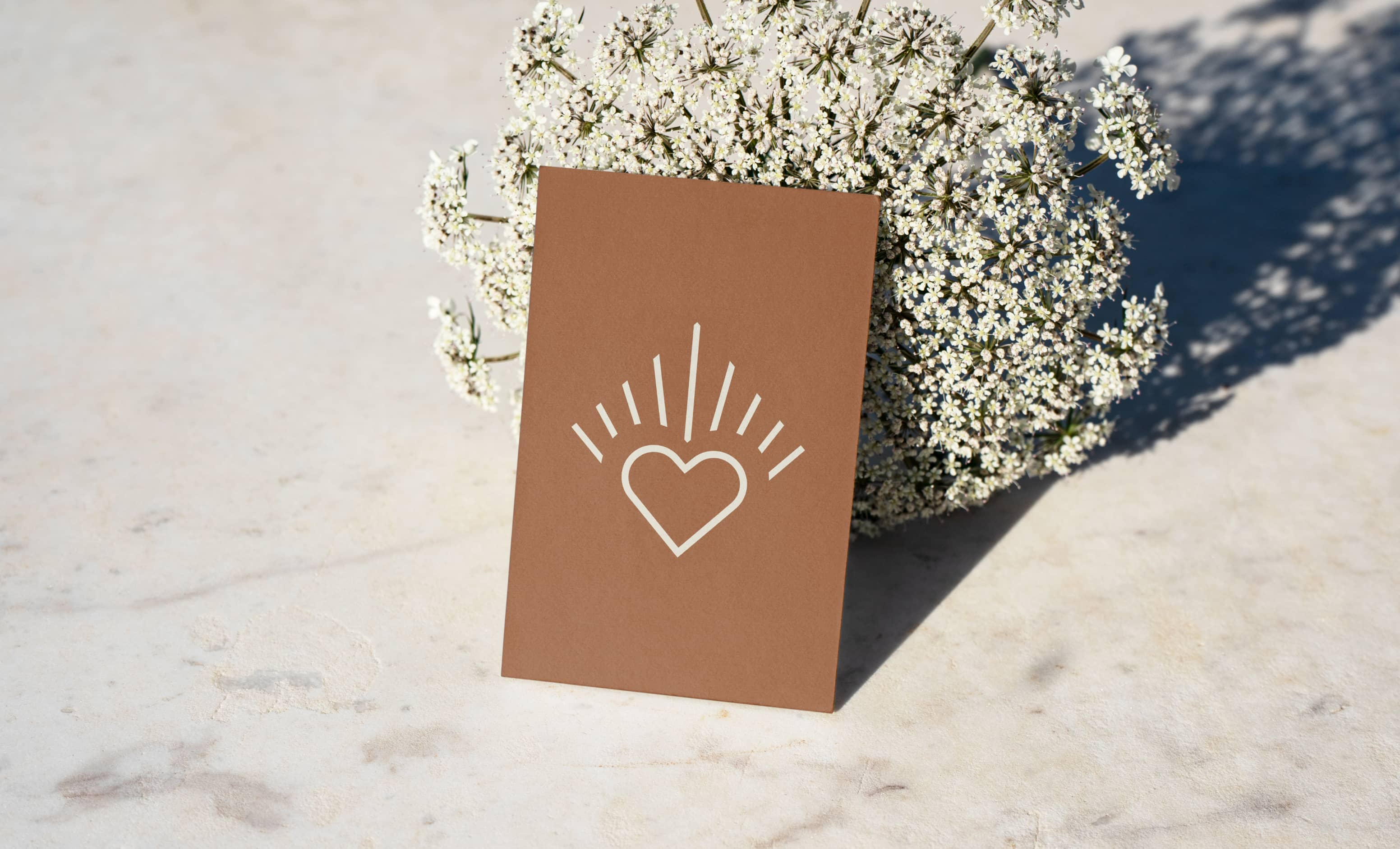 A brown business card with a heart-shaped icon resting on a bouquet of flowers