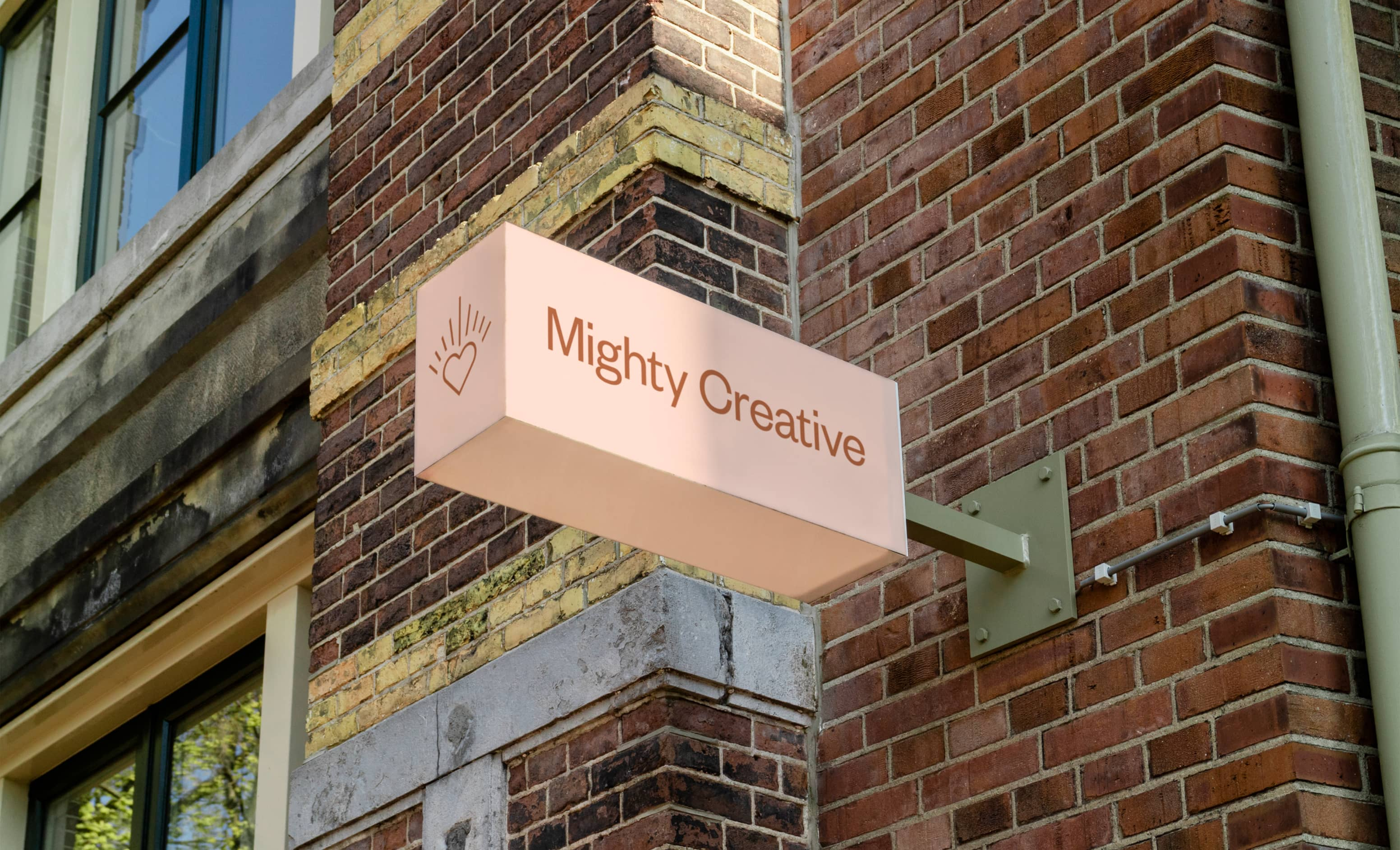 """A light pink coloured sign protruding from a red brick wall with the words """"Might Creative"""""""