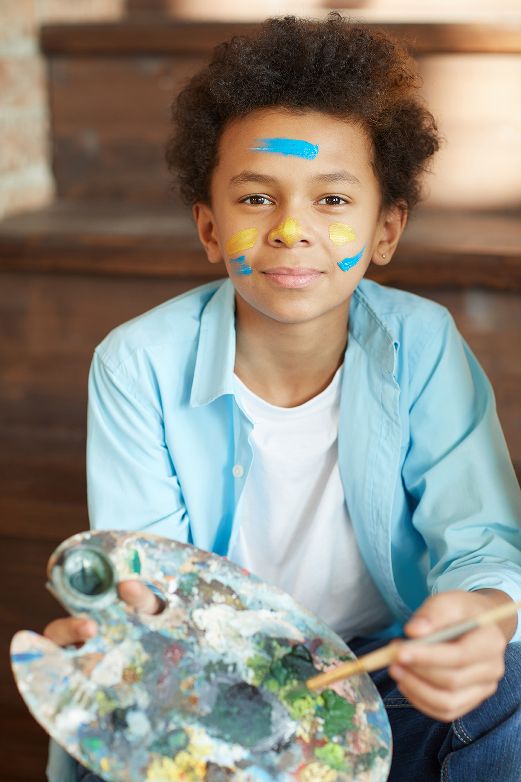 a handsome kids smiling with paint on his forehead holding a palette with paint.