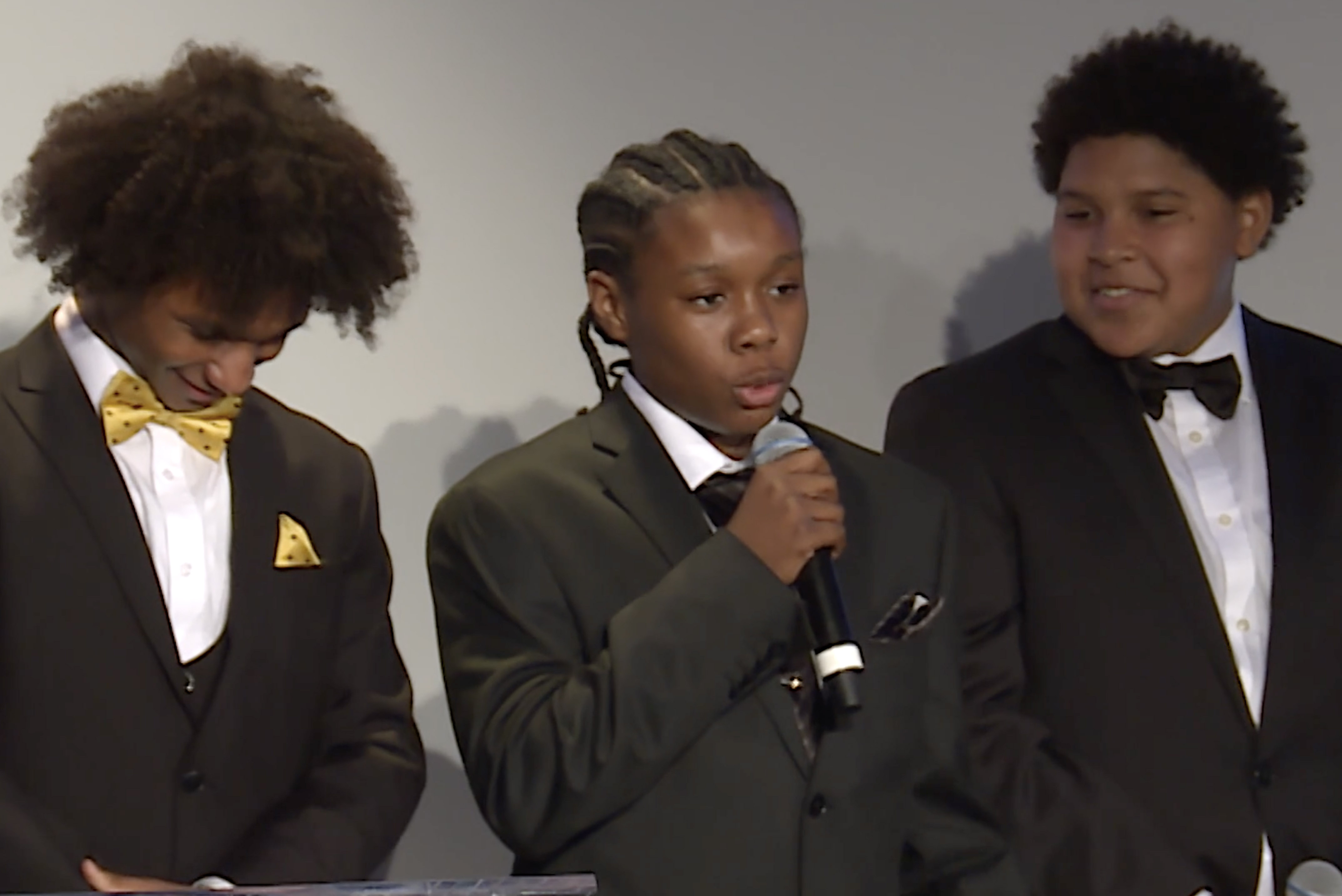 Three kids dressed in tuxes at a formal VE-JV event. The kid in the center is speaking on the mic.