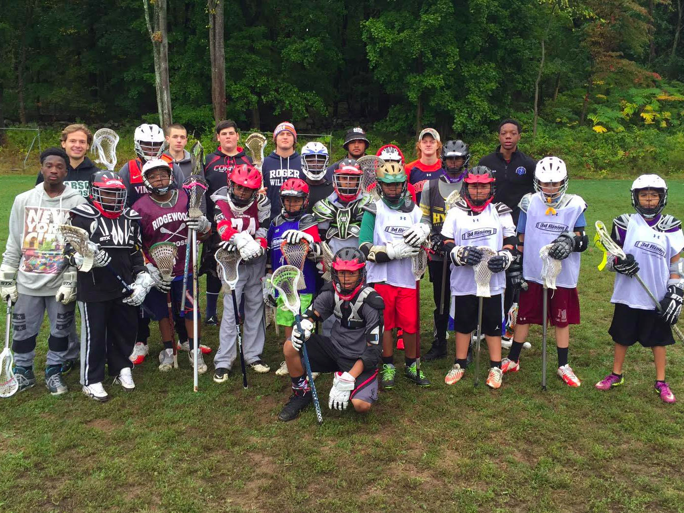 Sojourner Truth boys involved with Harlem Lacrosse gathered on the playing field.