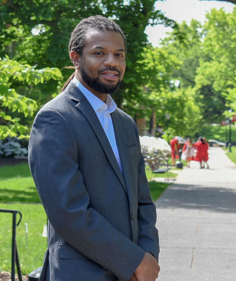Photo of Mr. Mario McMichael, wearing a suit and standing in a park with trees in the background.