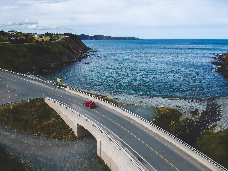 photo d'un paysage avec une voiture rouge qui roule sur la route