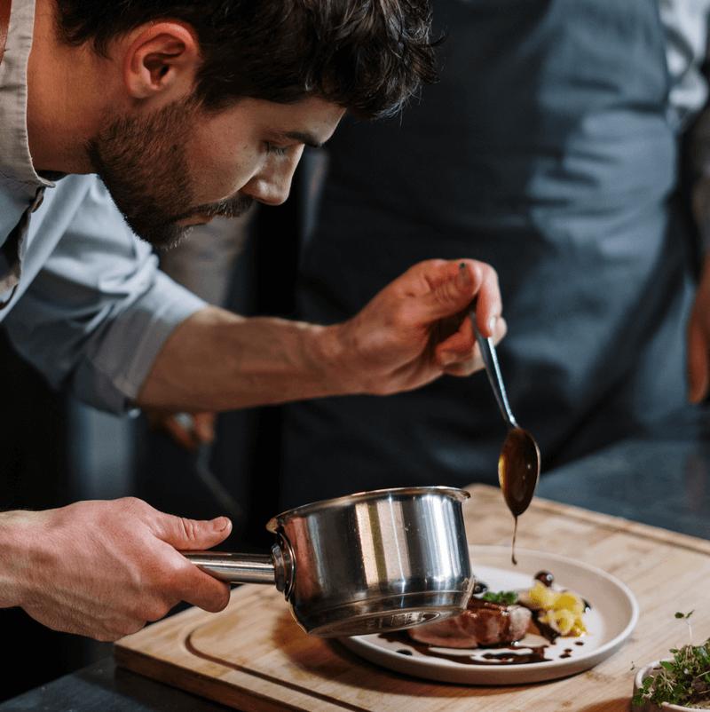 A chef garnishing in virtual restaurant.