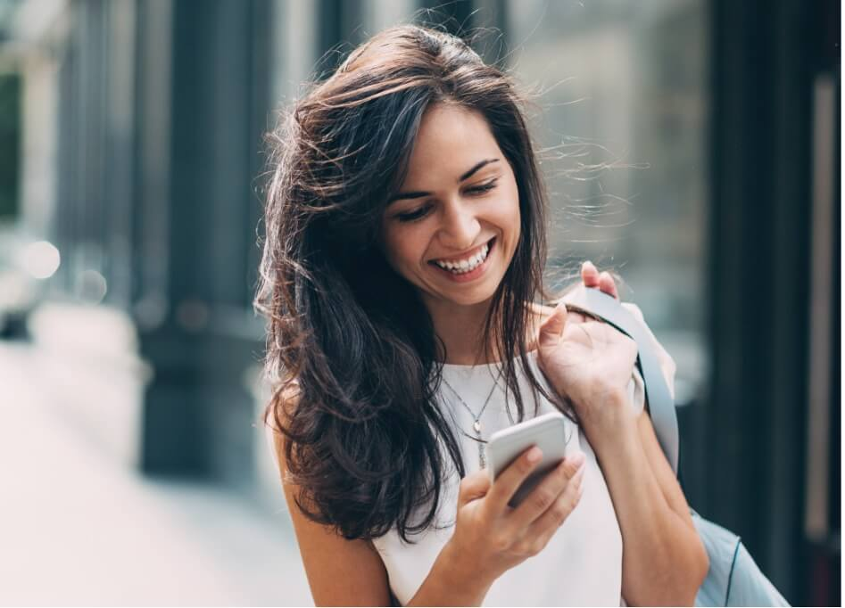 Woman With A Backpack Over Her Shoulder Smiling At Her iPhone