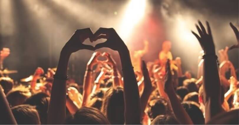 A Girl Making a Love Sign With Her Hands In A Festival Crowd