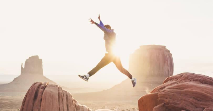 A Men Jumping Between Rocks In the Dessert