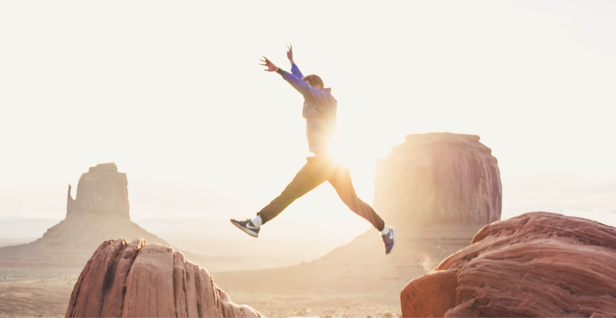 Man Jumping In the Air In Front Of Dessert Mountains On A Sunny Day