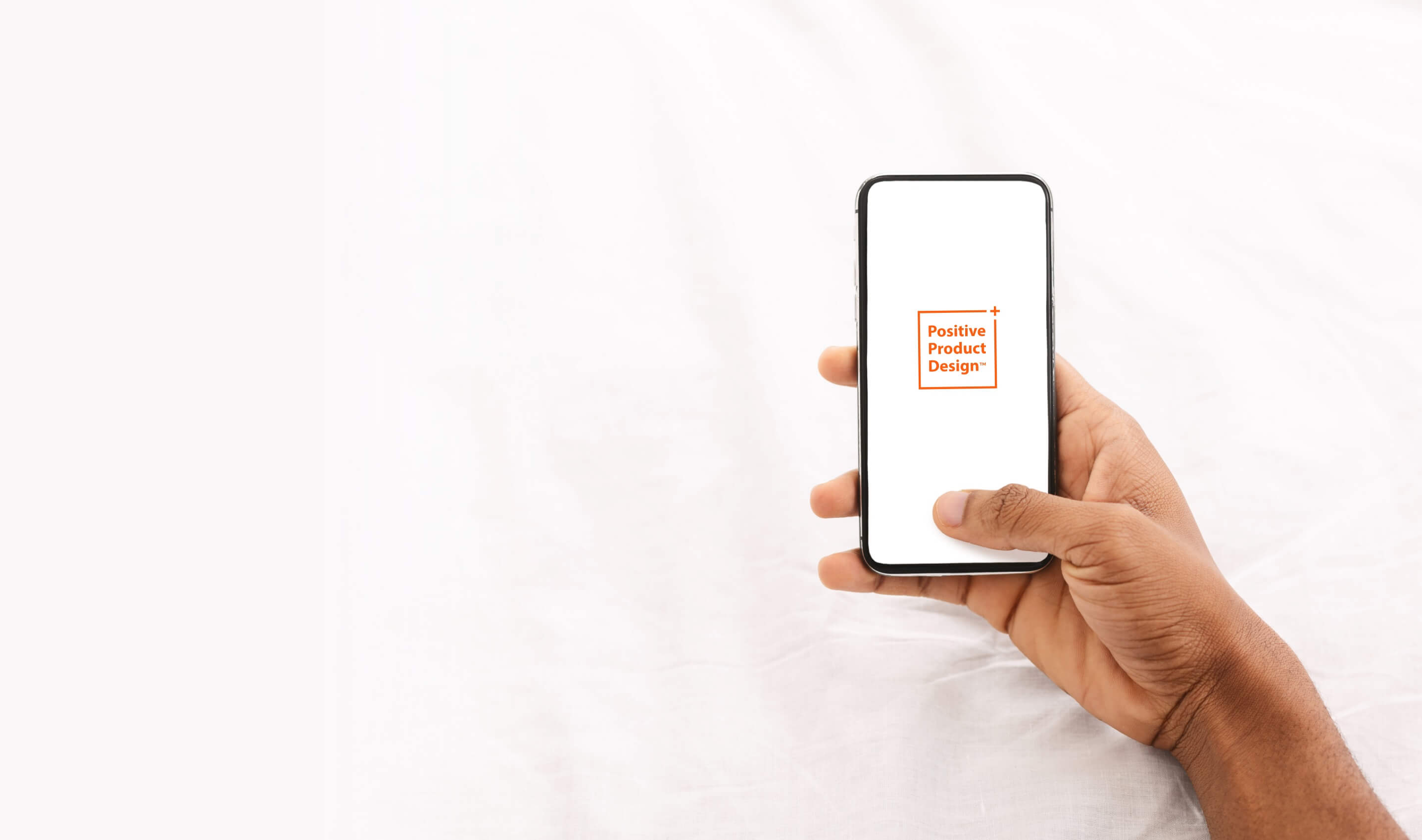 Man Holding an iPhone X In His Hand With the Positive Product Design Logo On The Screen