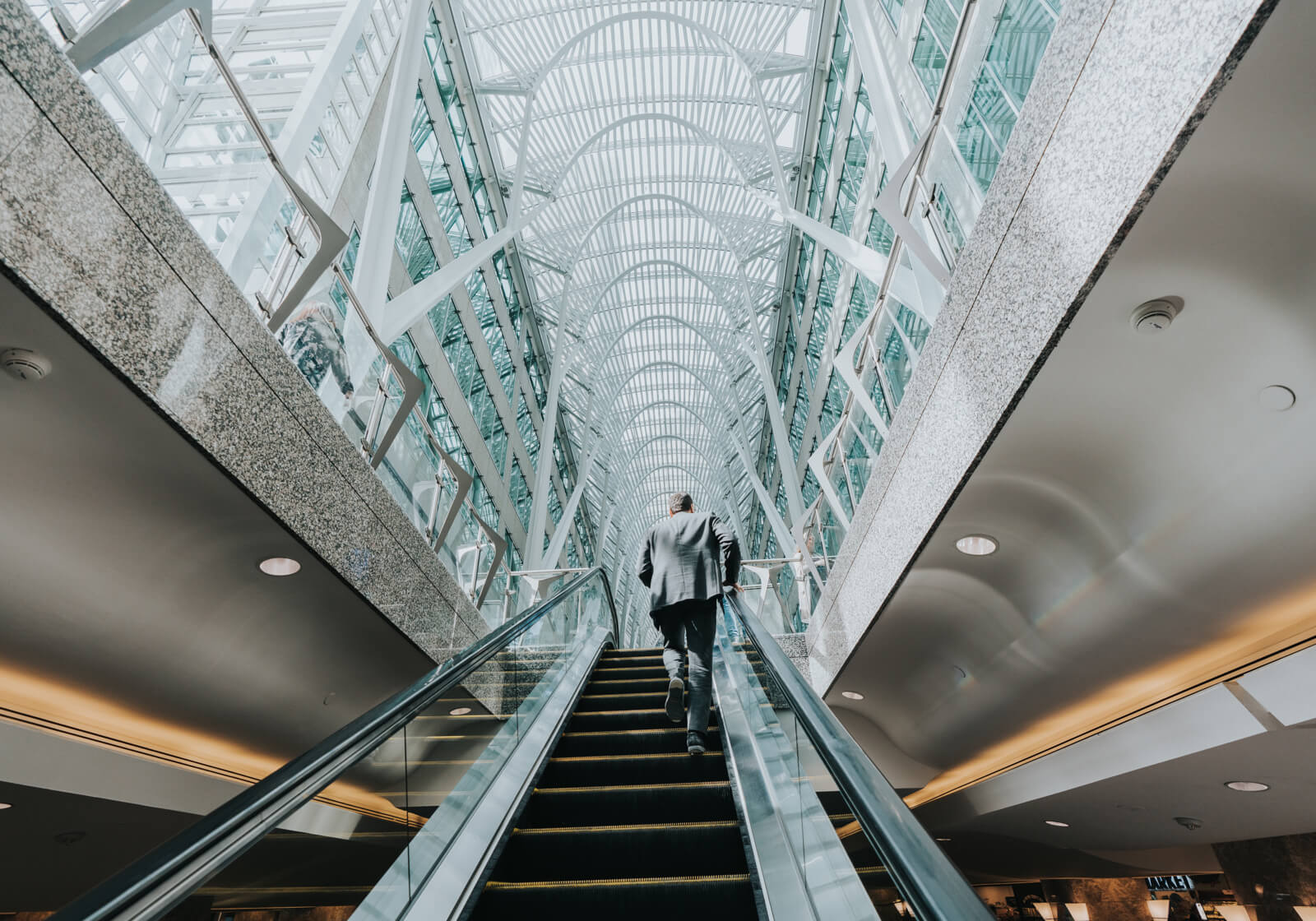 A man running up the escalator in bright office building