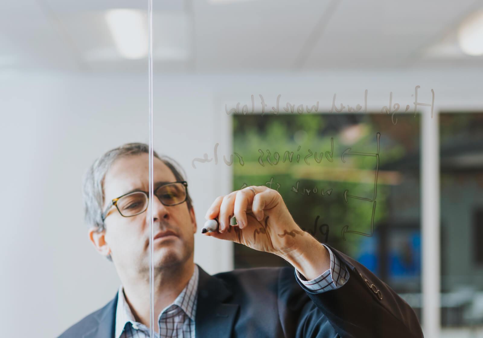 Professional man diagramming on glass wall