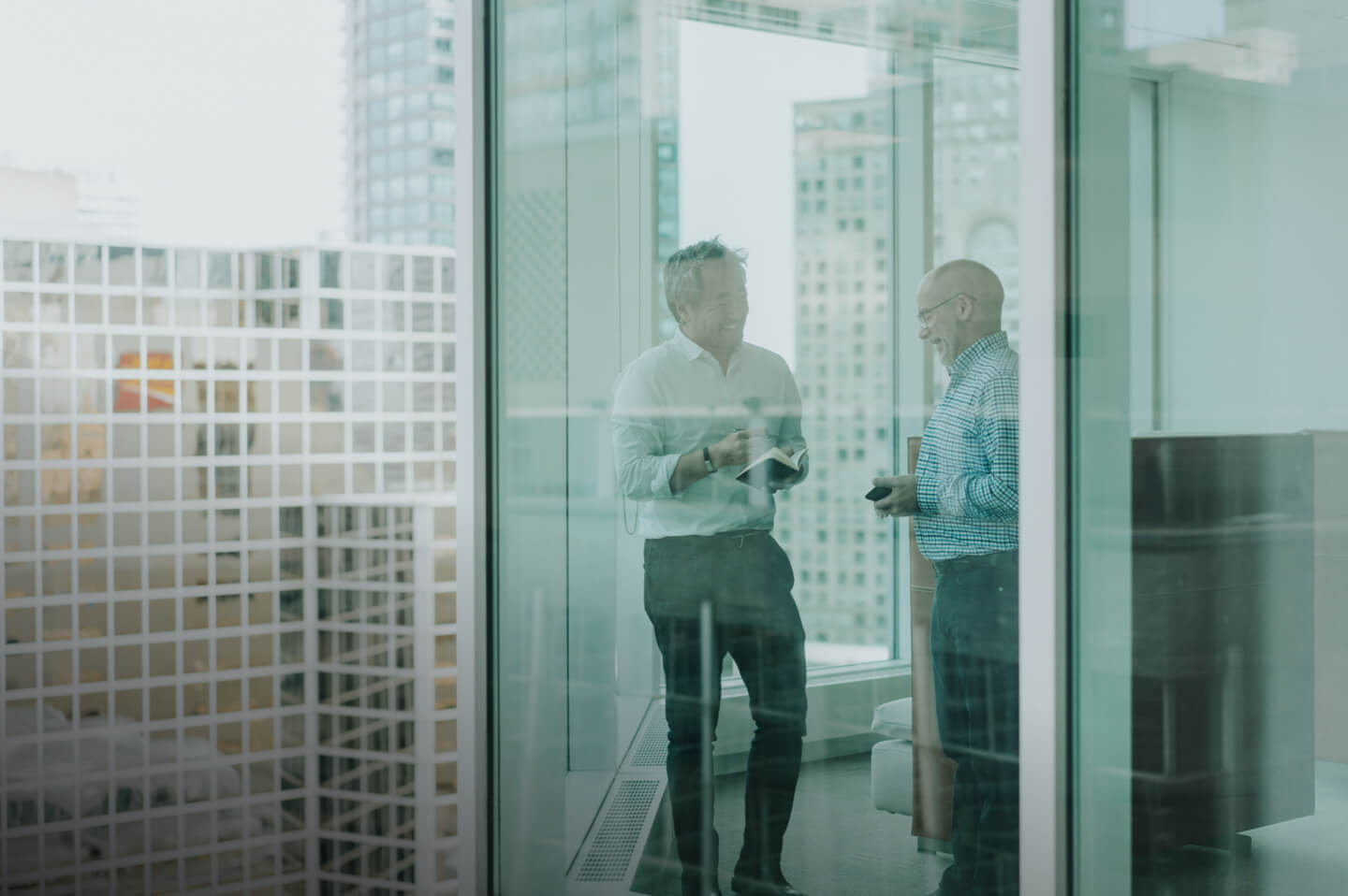 Two men standing in front of large glass windows having a conversation