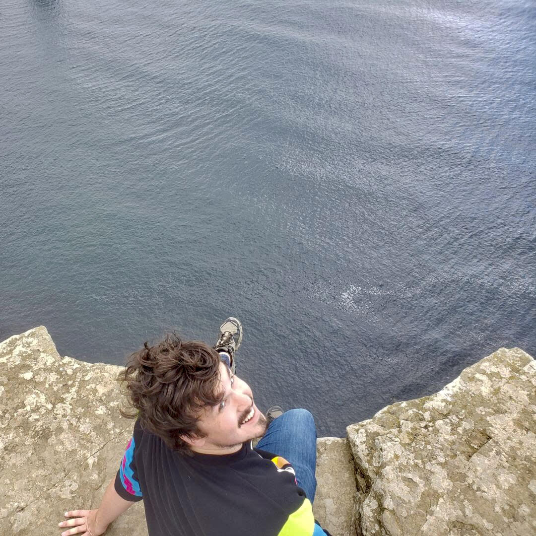 Mike Wilson sitting on the ledge at the Cliffs of Moher