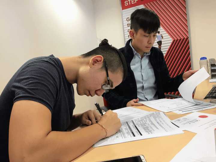 A photo of Shawn signing official documents to incorporate Tribeless in Malaysia.