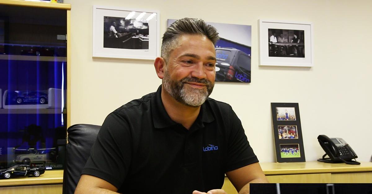Simon Lobina is pictured sitting at a desk inside his Ilkeston headquarters