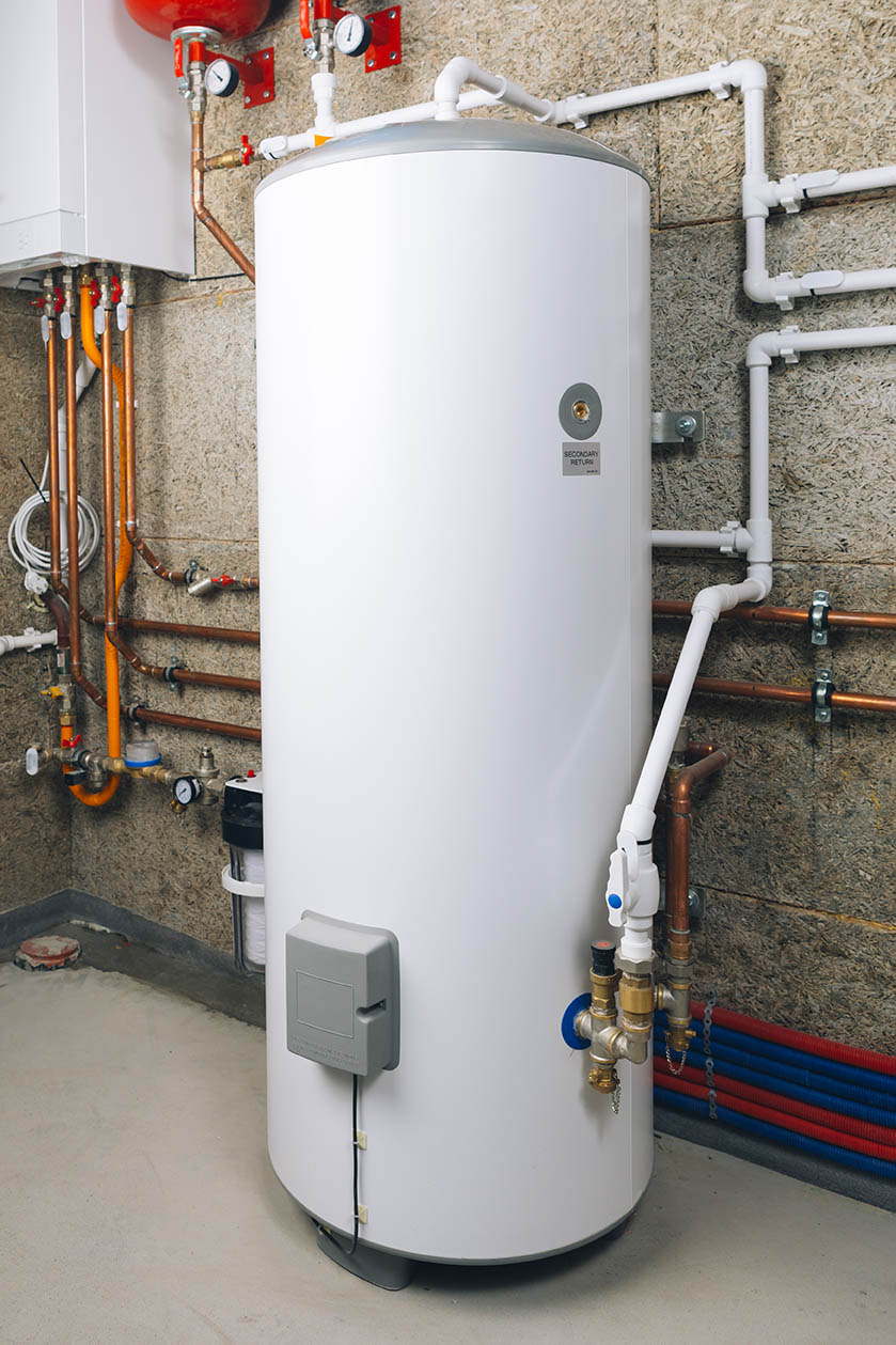 A white water heater in a basement