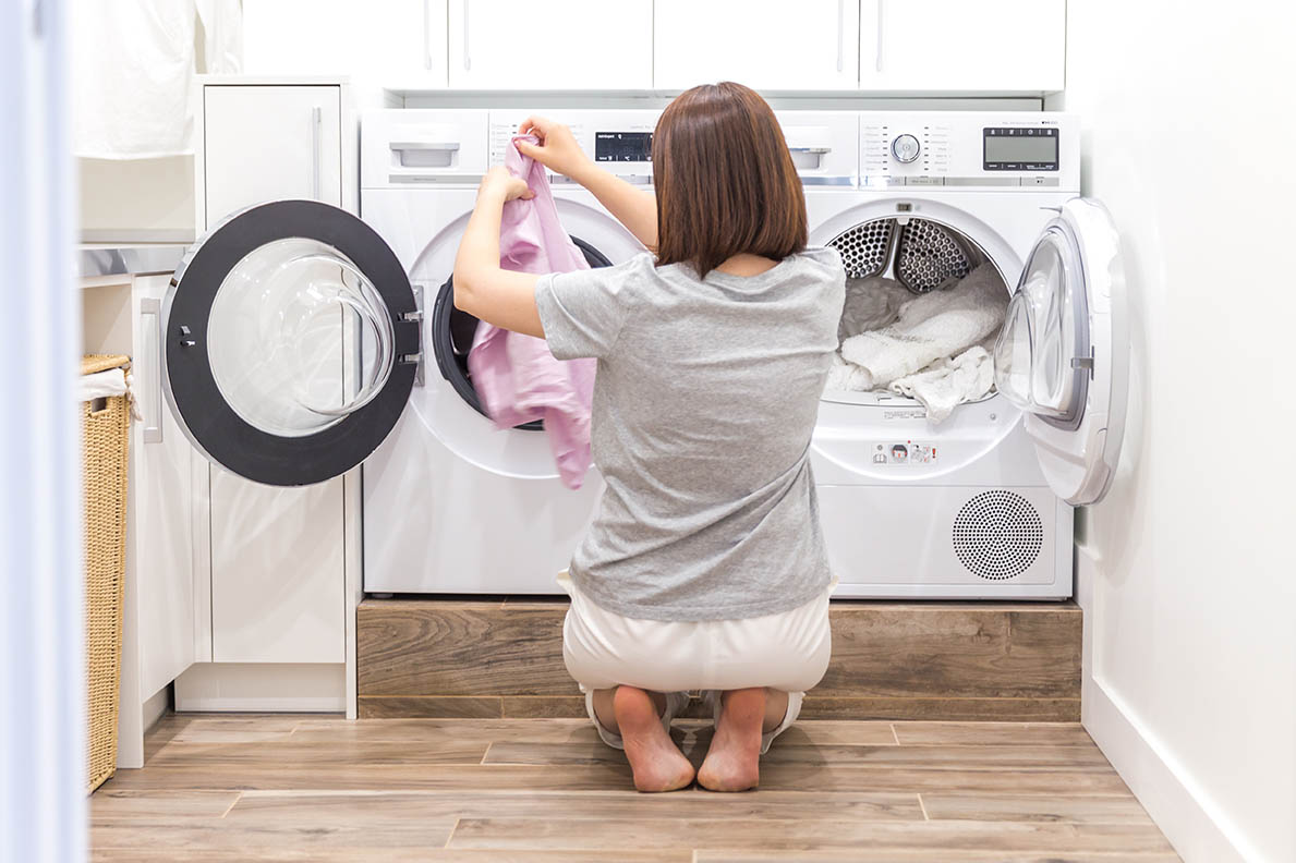 A woman moving laundry over from a washer to a dryer