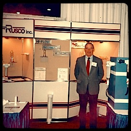 The founder of the company standing in front of some of his products.