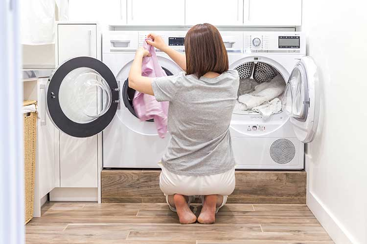 Woman moving laundry over from a washer to a dryer