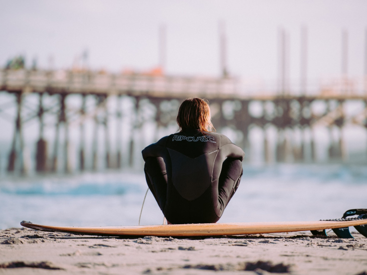 Man sitting on a surfboard looking over the sea